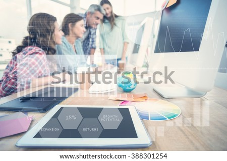Business interface with graphs and data against tablet in the foreground with business people in the background - stock photo