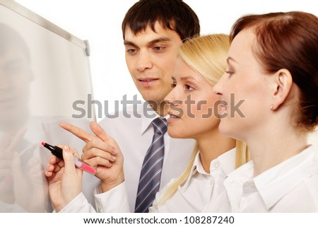 Business intern pointing at whiteboard and asking her boss to explain
