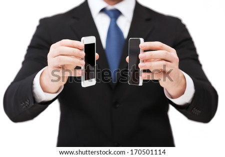 business, internet and technology concept - businessman showing two smartphones with blank black screens