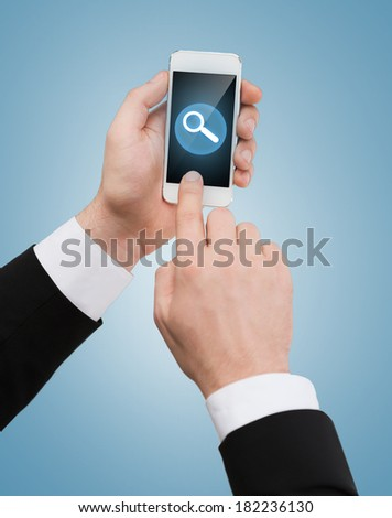 business, internet and technology concept - businessman touching screen of smartphone with magnifying glass - stock photo