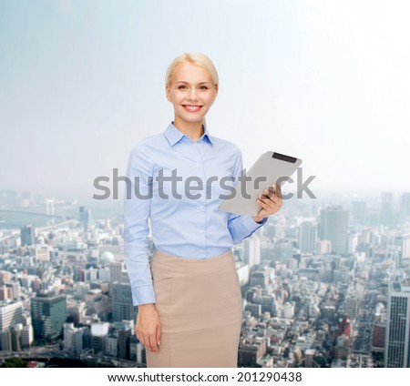 business, internet and technology concept - smiling woman looking at tablet pc computer