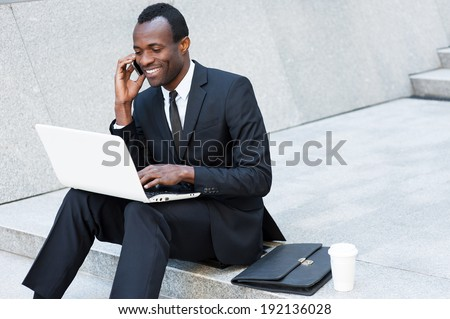 Business is his life. Cheerful young African man in formal wear talking on the mobile phone and working on laptop while sitting on outdoors staircase - stock photo