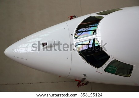 Business jet airplane cockpit glass and nose fairing. - stock photo