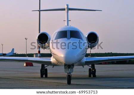 business jet on ground at sunset - stock photo