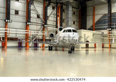 Business jet parked in the hangar - stock photo