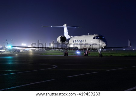Business jet starting up at night.