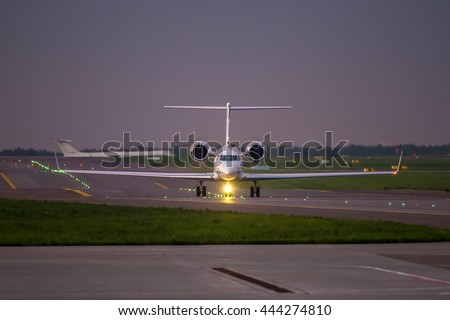 Business jet taxiing on airport runway while passenger aircraft taxiing for take off - stock photo