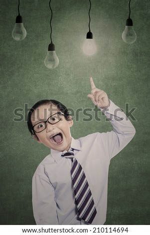 Business kid is pointing his finger at lit bulb in class - stock photo