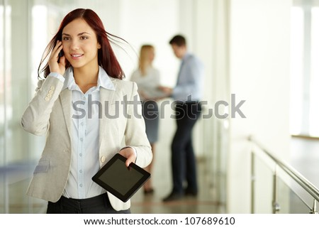 Business lady answering the phone with a smile with working team on background - stock photo