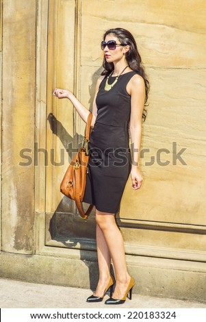 Business Lady. Dressing in black work dress, wearing sunglasses, necklace with golden pendant, leather shoes, arm carrying a brown bag, a young sexy businesswoman is standing outside, taking a break.