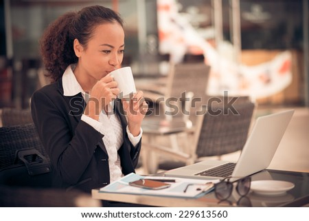 Business lady drinking coffee and working on laptop in the cafe - stock photo
