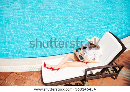 Business lady in red heels and swimming suit sitting in chaise-longue and working on laptop