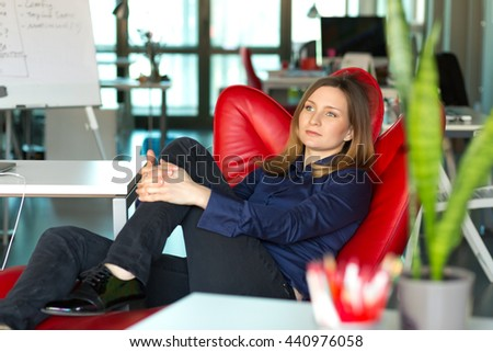 Business Lady in smart casual Clothing sitting in Relaxation Chair and thinking about strategic Decision at modern creative Industry Company Office Interior