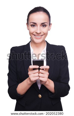 Business lady with mobile phone. Cheerful young woman in formalwear holding mobile phone and smiling while standing isolated on white - stock photo