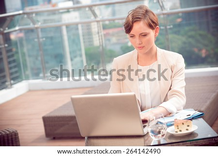 Business lady working on laptop in the cafe - stock photo