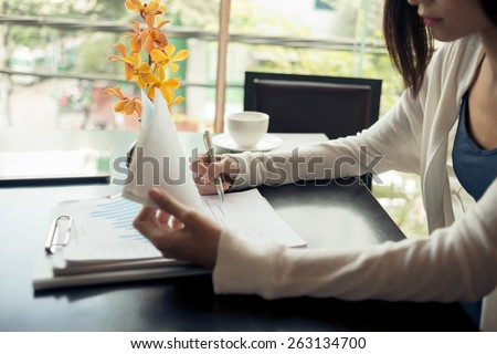 Business lady working with documents in a cafe