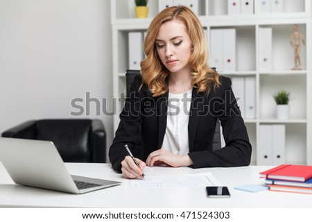 Business lady writing on piece of paper. Laptop and smart phone on desk. Shelves in background. Concept of office work