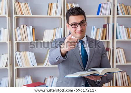 Business law student with magnifying glass reading a book
