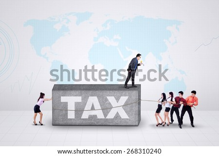Business leader commanding his employees to pull a tax burden together - stock photo