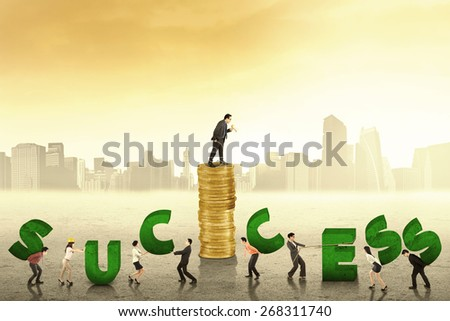 Business leader giving commands from a pile of golden coins on his employees to build a success text - stock photo