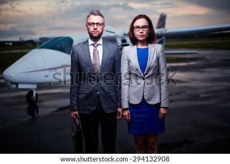 Business leaders in formalwear standing on arrival area and looking at camera - stock photo