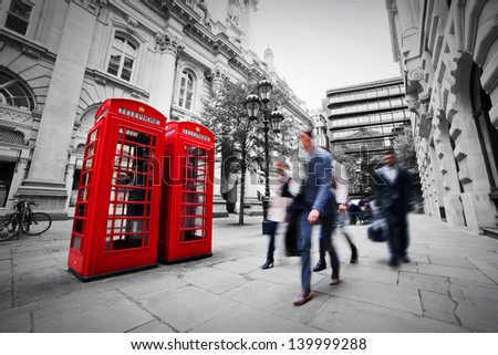 Business life concept in London, the UK. Red phone booth, people in suits walking - stock photo