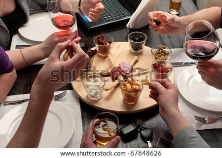 Business lunch - Group of people eating lunch of a set of delicious spicy snacks - stock photo