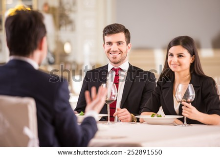 Business lunch. Team meeting in restaurant, eating and drinking in celebration of good work together. - stock photo