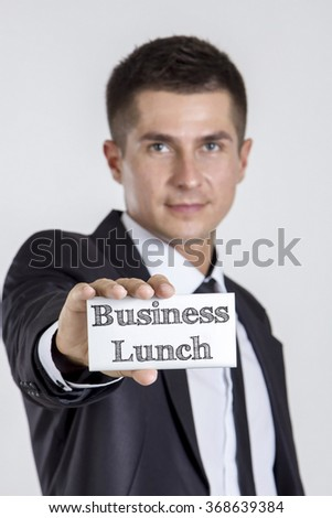 Business Lunch - Young businessman holding a white card with text - vertical image