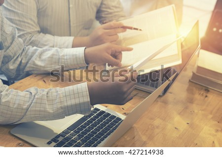 Business Male manager discussion ideas and writing business plan at workplace,man holding pens and papers for business plan,notes documents,business plan on the table,vintage color,selective focus. - stock photo