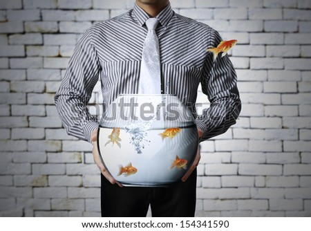 Business man a flying goldfishes - stock photo