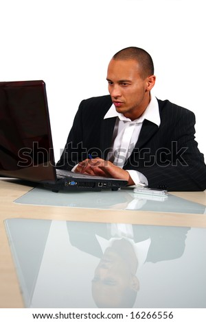 Business Man A young businessman sitting by desk at office working on the laptop with cellphone on the table. - stock photo