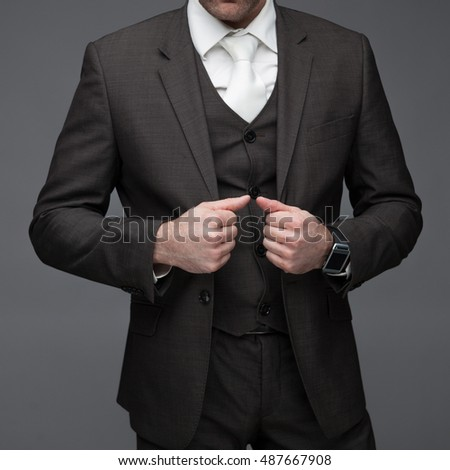 Business man about to button his jacket, on a grey background, stock picture