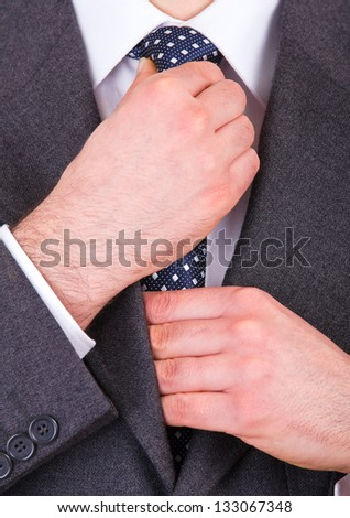 Business man adjusting his necktie. - stock photo