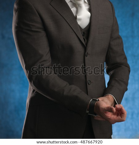 Business man adjusting his sleeve, on a blue background, stock picture