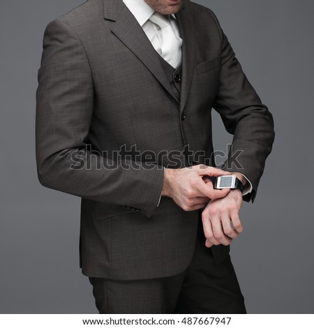Business man adjusting his watch, on a grey background, stock picture