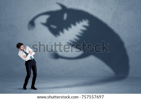 Business man afraid of his own shadow monster concept on grungy background
