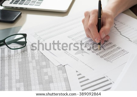 business man analyzing  diagrams  and graphs with laptop computer on glass table and books at background