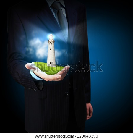 Business man and a lighthouse shining in darkness - stock photo