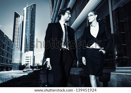 Business man and business woman are walking the streets of the big city. - stock photo