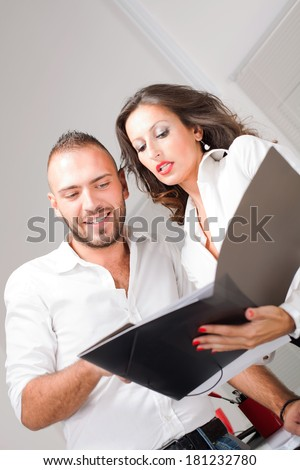 Business man and business woman looking in folder and talking about business project