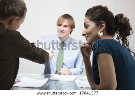 Business man and business woman shaking hands - stock photo