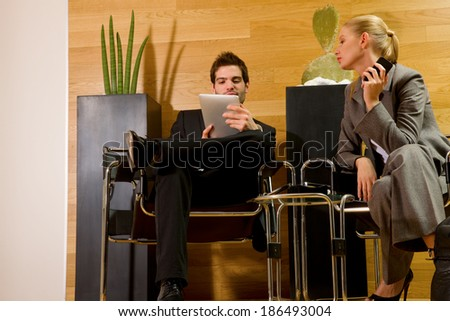 business man and business woman waiting in office lobby - stock photo