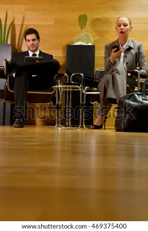 business man and business woman waiting in office lobby