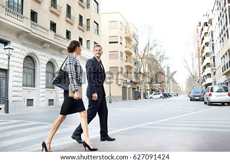 Business man and business woman walking together in city financial street, talking and smiling outdoors. Elegant professional people wearing suits, working lifestyle exterior. Dynamic office workers.