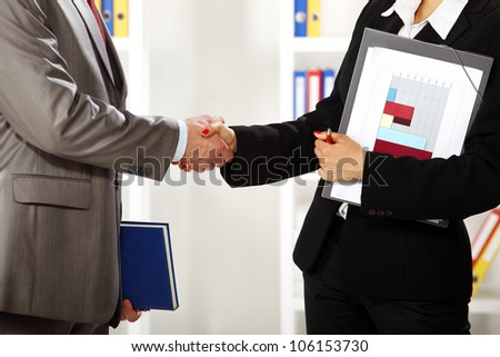 Business man and business women in the office she is standing and shaking hands close up - stock photo