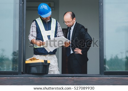 business man and engineer looking at a plan,Standing by the window