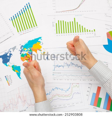 Business man and financial data - thumbs up - stock photo