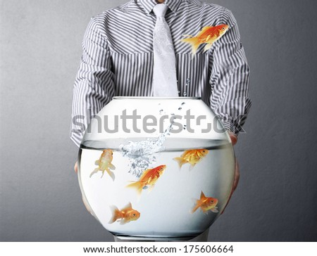 Business man and flying goldfishes from one to another  - stock photo