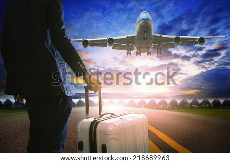 business man and luggage standing in airport and passenger jet plane flying over runway against beautiful sky use for air transport and travel by airline topic